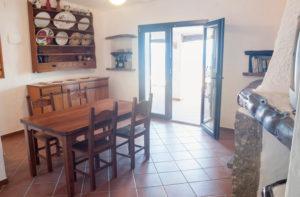 2.Salone, con tavolo e piattaia in stile sardo. La pala presente sul soffitto può essere una valida alternativa per chi non ama l'aria condizionata.